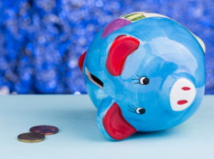 piggy bank on its side with a couple of coins