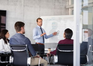 businessman explaining on a white board in a meeting