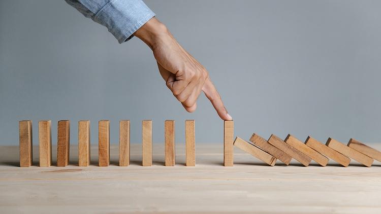 man stops dominos falling