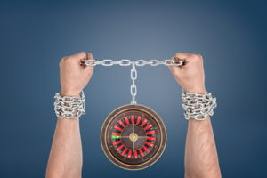 hands in chains tied to a roulette wheel